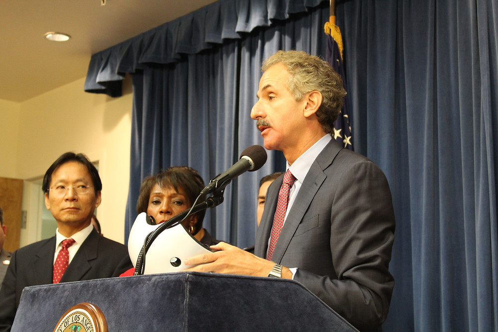 City Attorney Mike Feuer at podium leading a press conference holds a bike helmet that has been recalled.