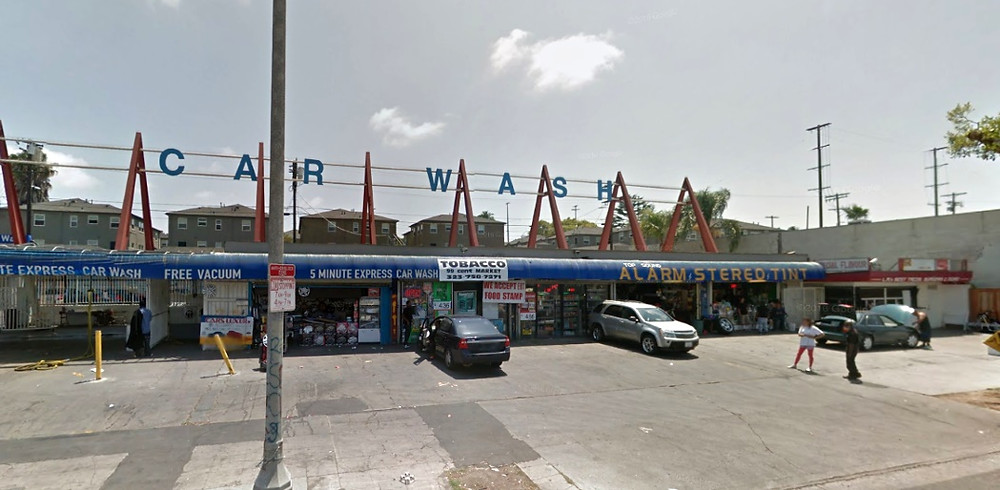 """A strip mall with three cars in the parking lot in front of it and several stores including a tobacco store, and car wash' the words """"Car Wash"""" run across the length of the top of it."""