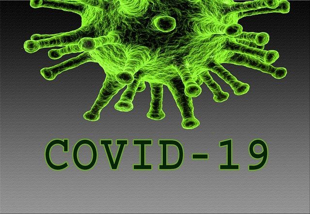 "An artists' graphic depiction of a green and black COVID-19 cell with spikes and the words ""COVID-19"" under it."