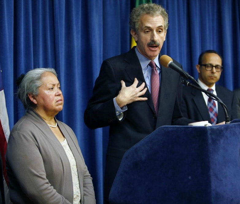 Photo of Los Angeles City Attorney Mike Feuer (center) with Rigo Reyes of the L.A. County Department of Consumer and Business Affairs and a local victim of immigration fraud
