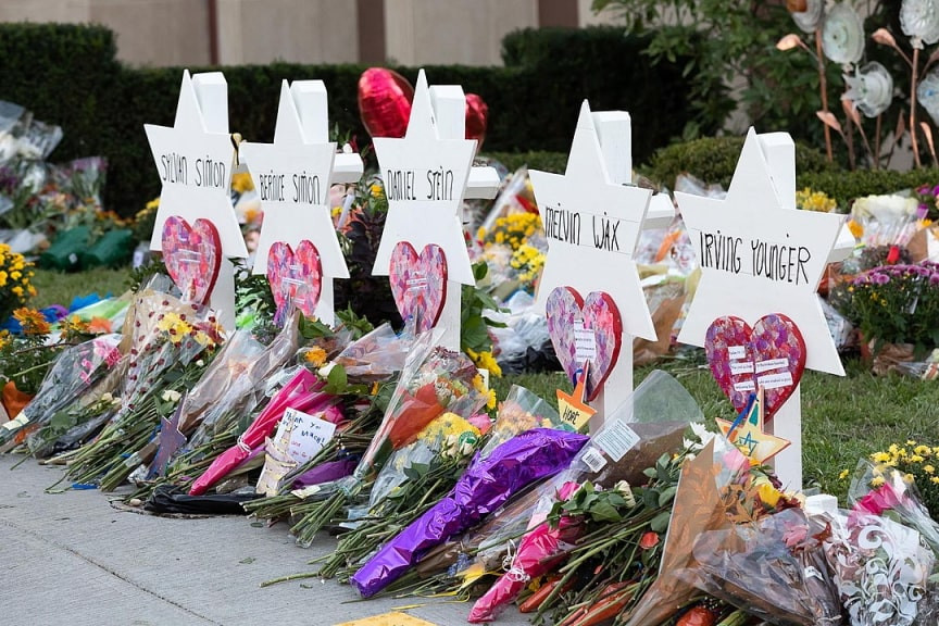A memorial of of white wooden menorahs with names on them and flowers in front of them marking the shooting at Tree of Life Synagogue in Pittsburgh.