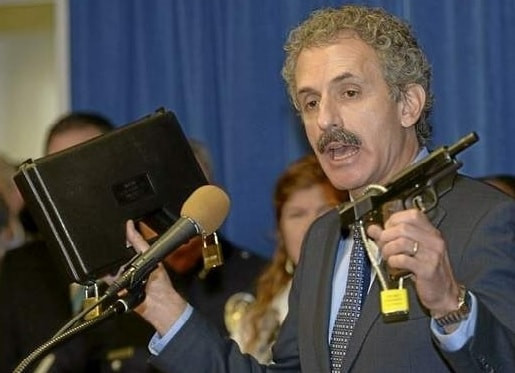 City Attorney Mike Feuer at podium with a gun and gun case, file photo