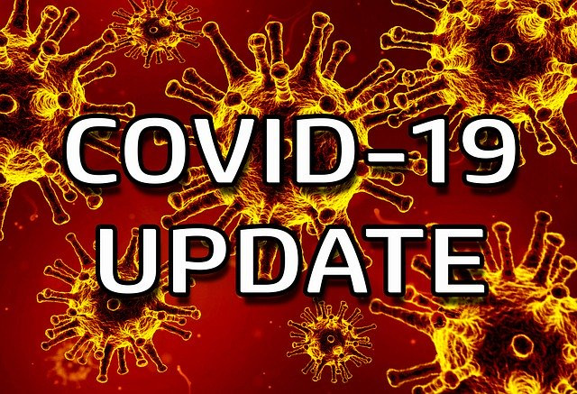 "Graphic that says ""COVID-19 Update"" in white letters against a red and orange background of COVID spiked cells."