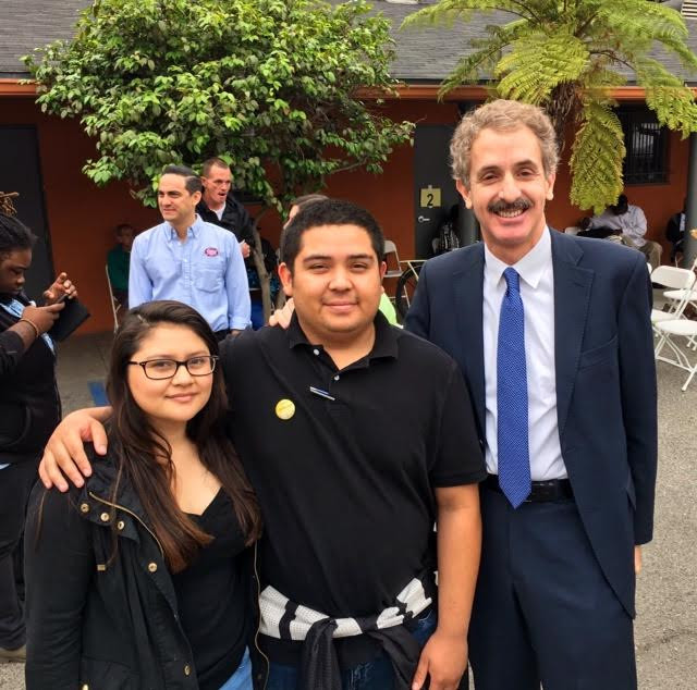 A young woman in a black leather jacket, a taller man in a black polo shirt and a taller man in a suit and tie next to them at an outdoor community event..