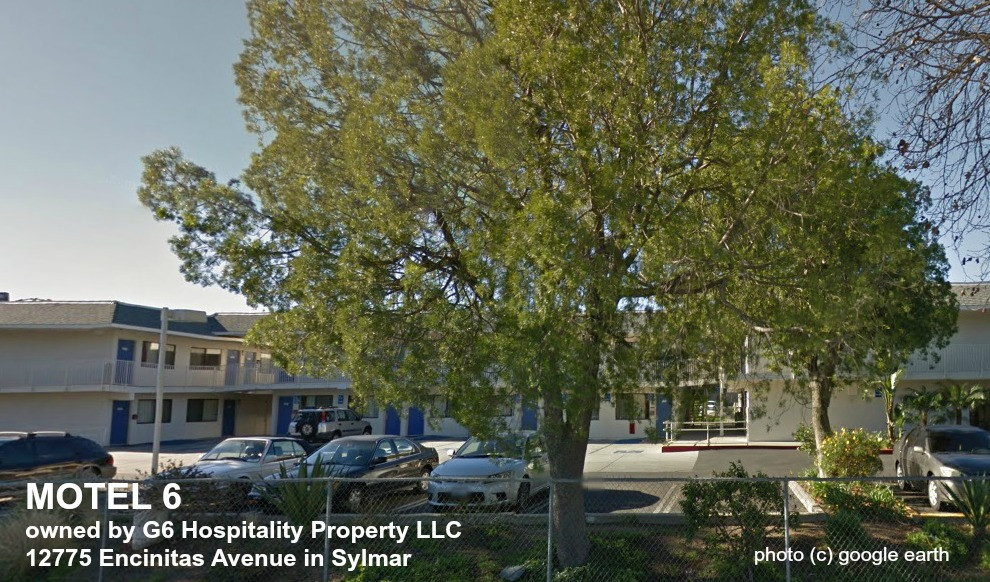 A two-level L-shaped motel with a parking lot with 5 cars in it and a big tree in front of it in Sylmar, taken from Google earth.