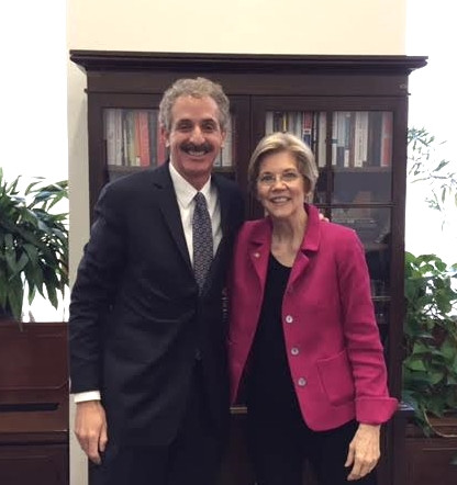City Attorney Mike Feuer in a dark standing with Senator Elizabeth Warren in a pink jacket in front of a bookcase and both are smiling.