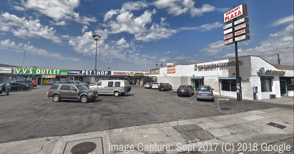 A strip mall with a sign that says Vermont Plaza, with about 10 cars in the parking lot and stores with signs on them, including Pet Shop, Tongs, V.V.'s Outlet.