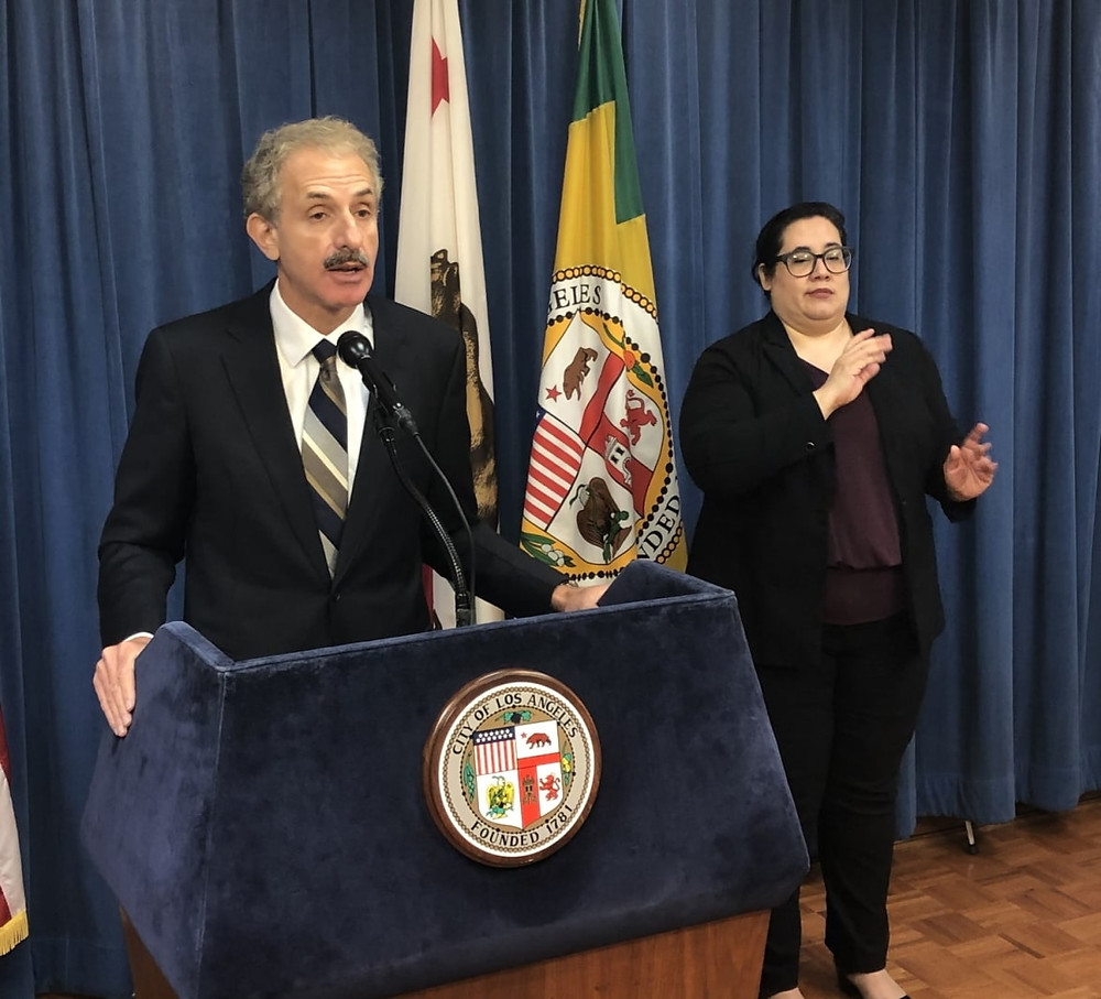 Los Angeles City Attorney Mike Feuer in a dark suit and tie standing at podium, speaking into a microphone, with an American Sign Language translator in black to his right.