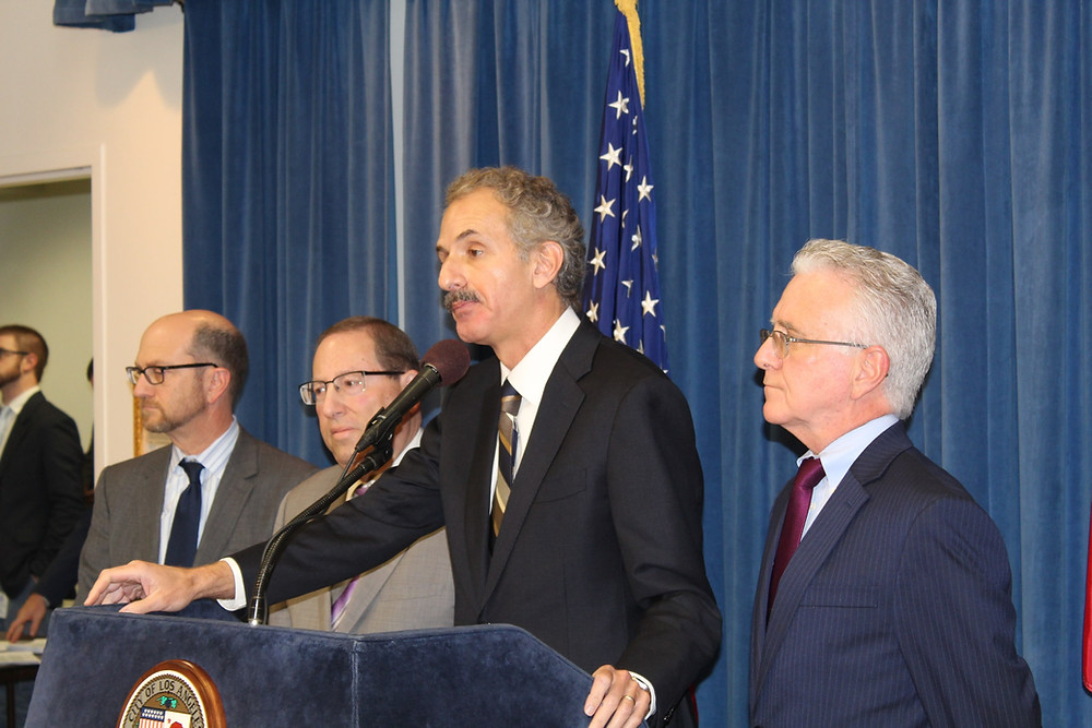 City Attorney Mike Feuer and three other men at podium.