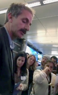 Man in a suit jacket and shirt standing in an airport terminal next to a number of people, one of whom appears to be crying.
