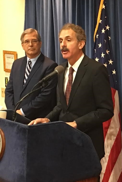 Man with a mustache in a dark suit, white shirt and maroon tie speaking into a microphone at a press conference, in front of a blue curtain and American flag with a man in a blue suit to his right.