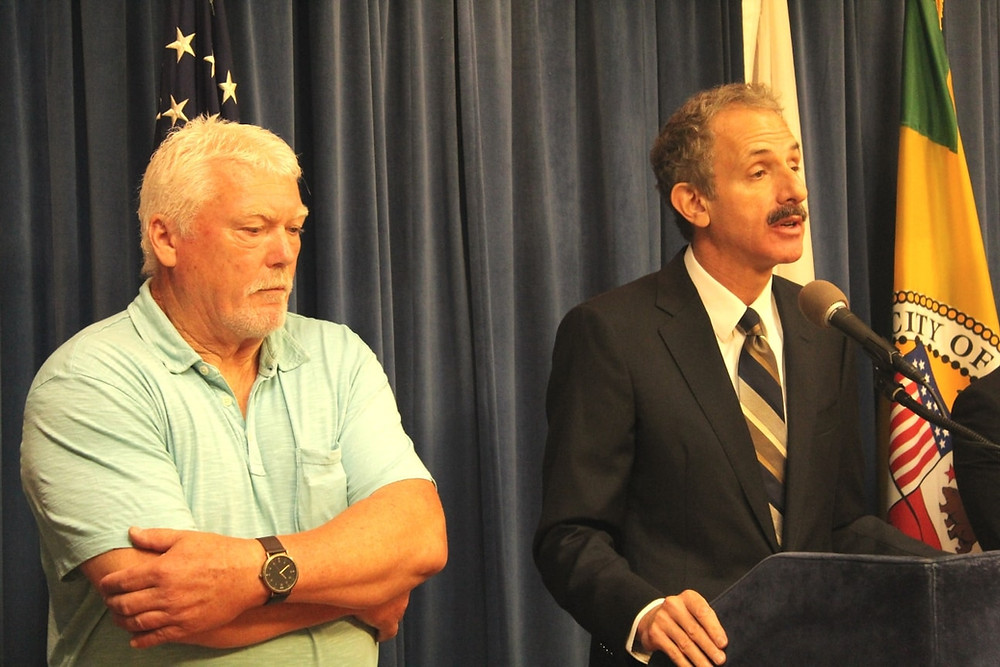 Older gentleman with his arms crossed next to City Attorney Mike Feuer, at podium