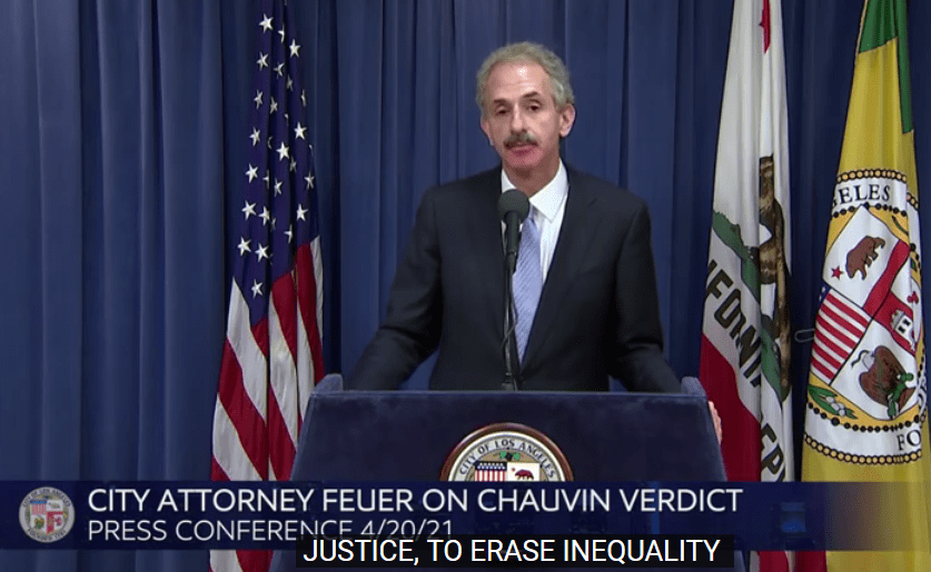 City Attorney Mike Feuer in dark suit and white suit standing a blue podium, speaking into a microphone in front of an American flag, the flag of the State of California and the flag of the City of Los Angeles.