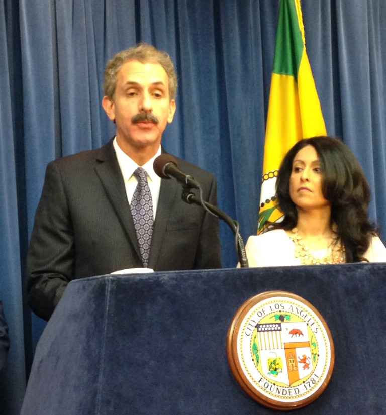 Los Angeles City Attorney Mike Feuer at a blue podium in a dark suit with Councilmember Nury Martinez on his left, both in front of a dark blue curtain and flag of the State of California.