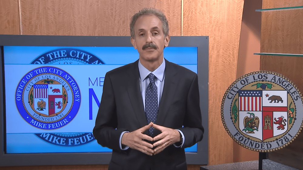 City Attorney Mike Feuer in front of a video monitor with the City of Los ANgeles seal to his right.