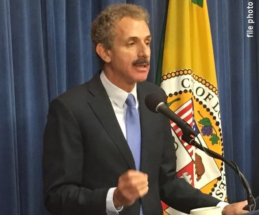 File photo of Los Angeles City Attorney Mike Feuer in a dark suit and lavender tie speaking into a microphone in front of the California state flag.