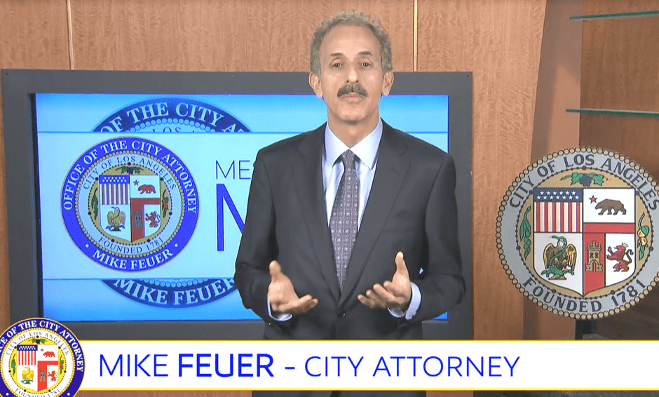 CIty Attorney Mike Feuer in a dark suit and purple tie standing in front of a television monitor with the official seal of the CIty Attorney's Office.
