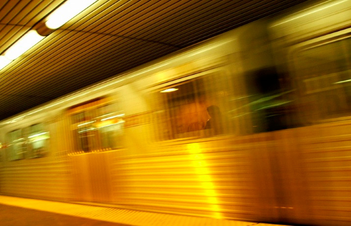 Stock photo of a blurry quick moving train with flourescent lights on the ceiling above it.