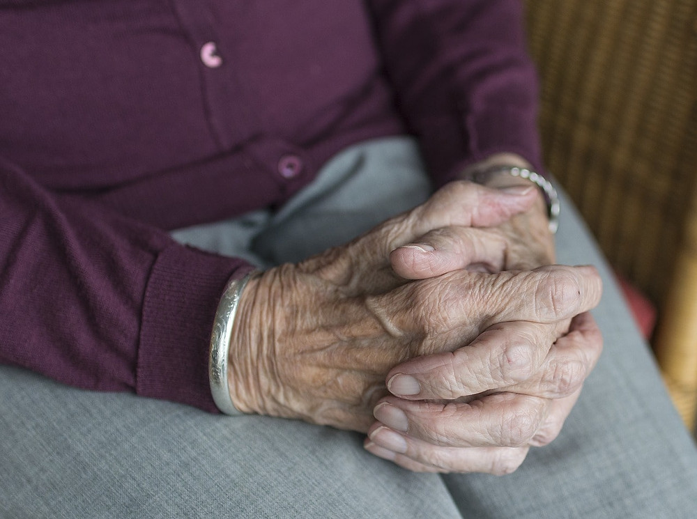Wrinkled hands of an elderly person folded in their lap, sitting atop gray pants.