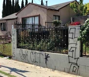 A white fence in front of a house with graffiti scrawled on it.