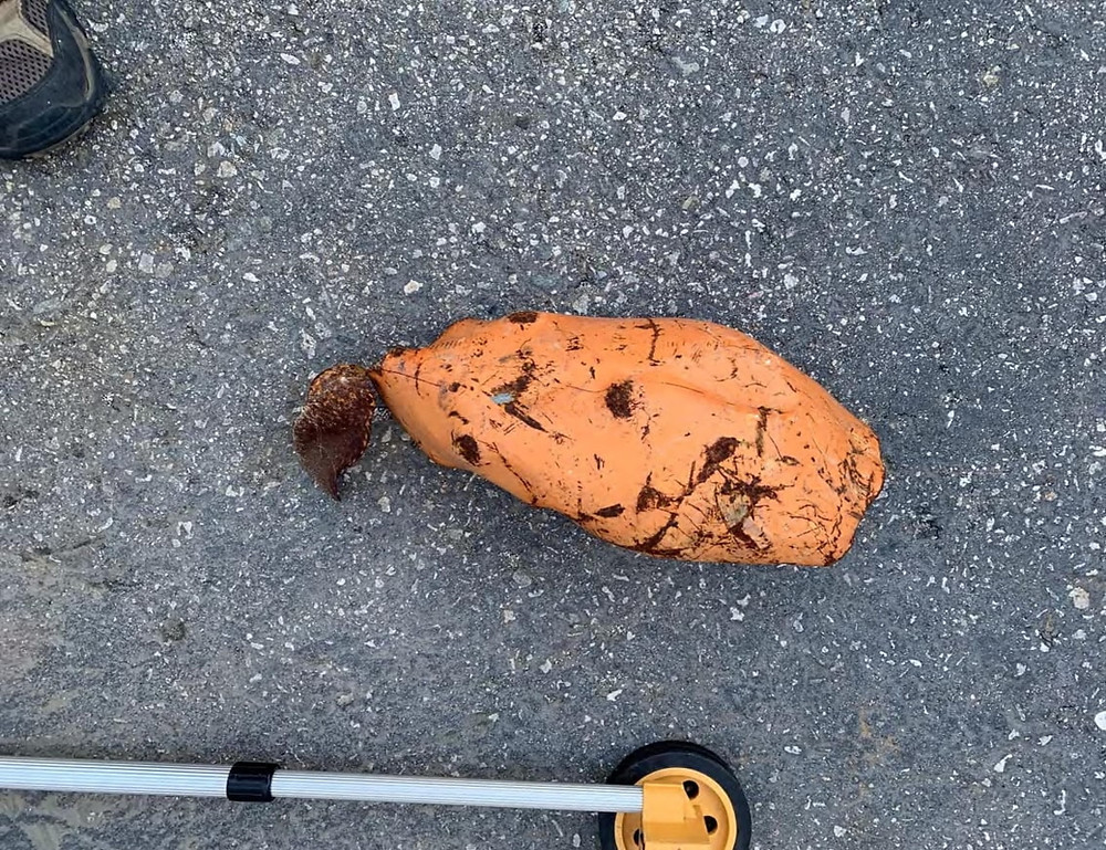 An orange, rusty piece of scrap metal on the ground on the campus of Jordan High School, allegedly launched from Atlas Metal which is next door to the school.