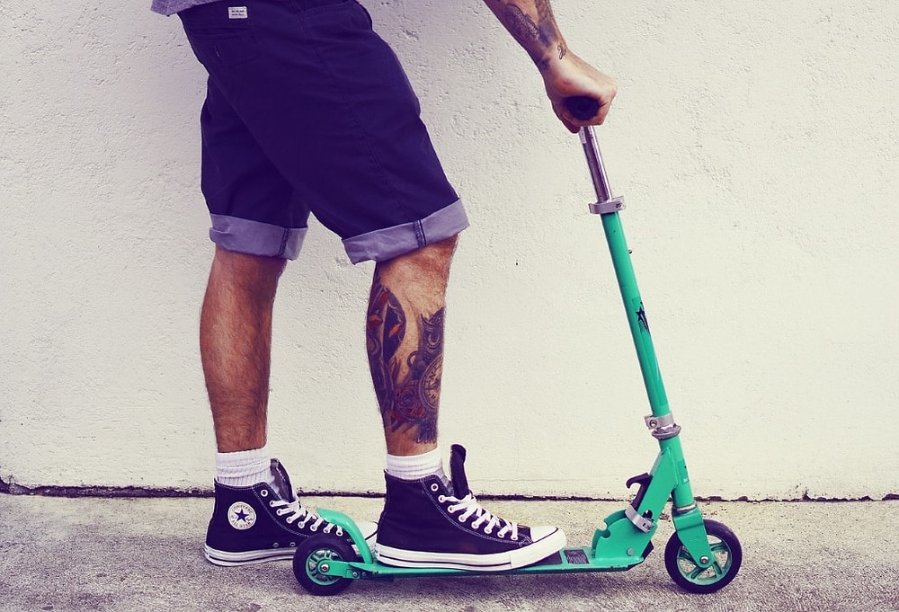 Stock image of a man's legs in denim shorts and with tattoos on a green scooter.