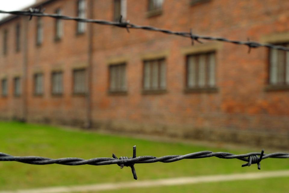 Stock photo representing a Concentration Camp: Two rows of barbed wire very close-up in front of a blurry red brick building in the background.