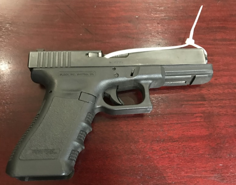 A dark gray metal handgun on a table which had been confiscated from a high school student.