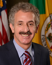 Official photograph of Los Angeles City Attorney Mike Feuer, in front of the American flag and the flag of Callifornia, in a dark suit with a light blue shirt and red and blue tie.