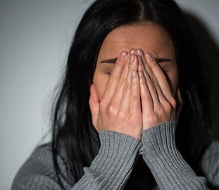 A woman in a dark gray sweater with her hands over her face, intimating shame or sadness.
