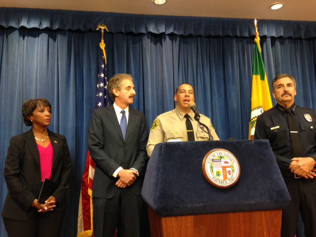 Four people standing in front of a room behind a blue-topped podium with the City of LA seal affixed to it, two - a woman and a man are wearing business attire, the other two are wearing police uniforms.