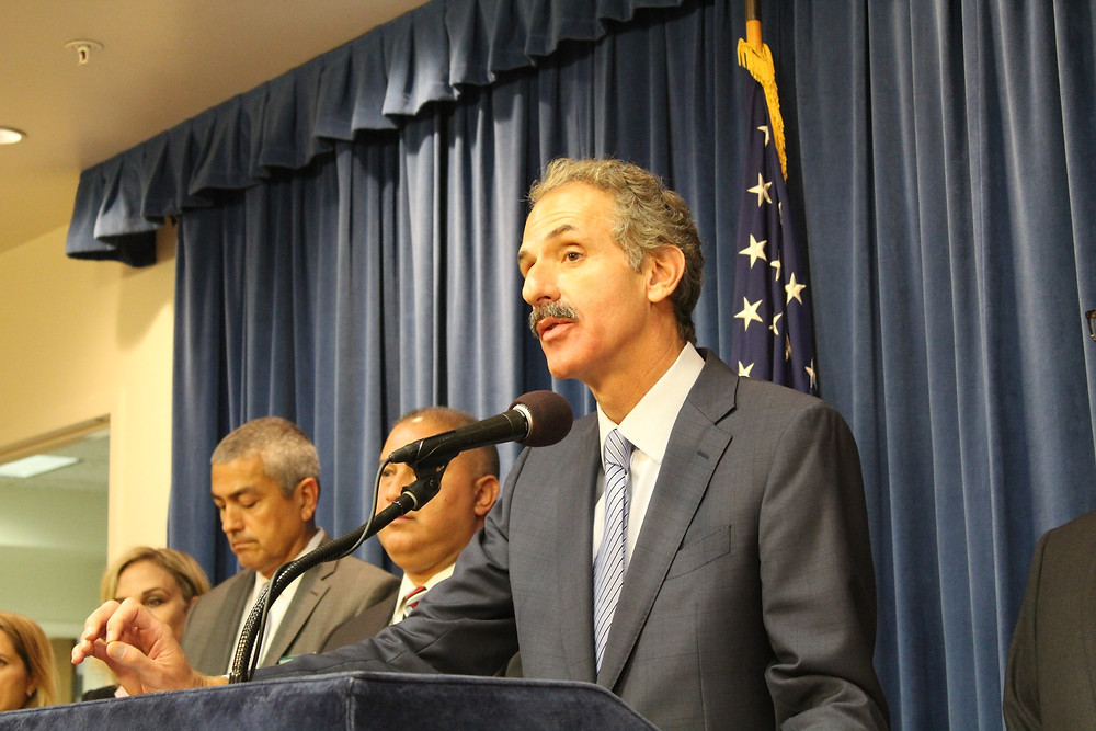 City Attorney Mike Feuer at podium leading press conference.