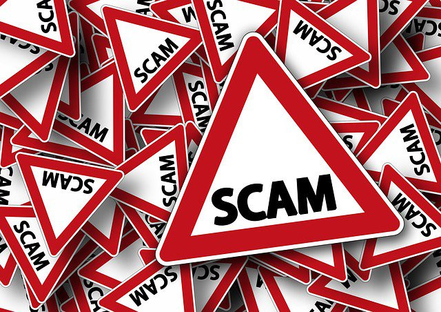 """A graphci with dozens of red and white signs signifying """"alerts"""" and with the word SCAM written on them."""