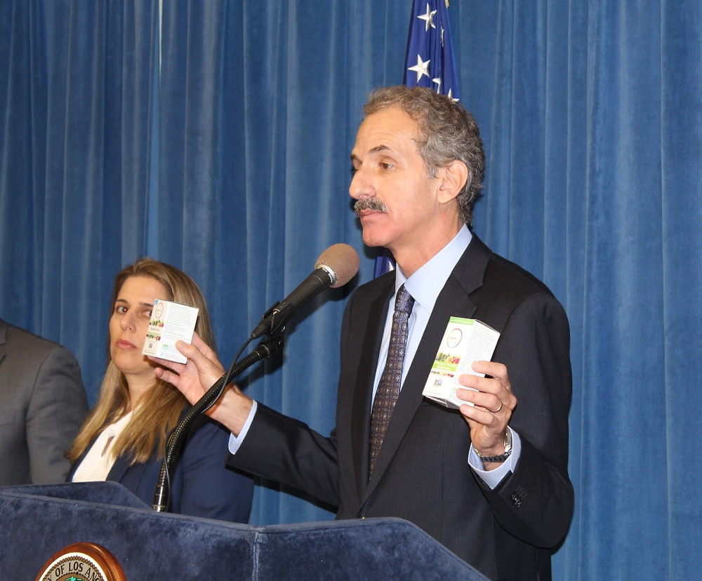 City Attorney Mike Feuer displaying Rainbow Light brand prenatal vitamins at press conference.