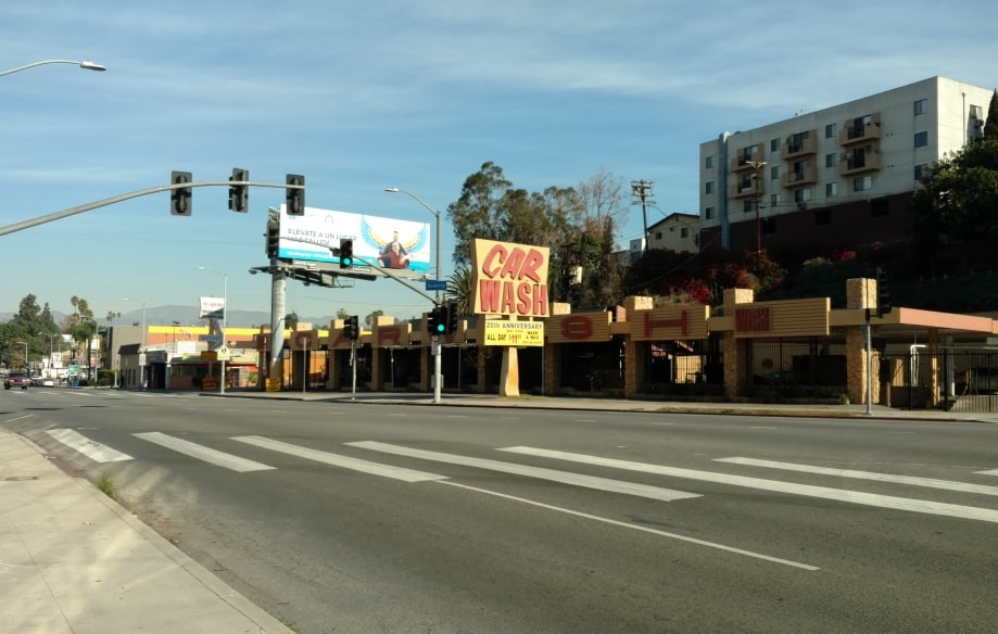 """An empty Beverly Boulevard, across the street from Silver Lake Car Wash, which has an old fashioned """"CAR WASH"""" sign."""