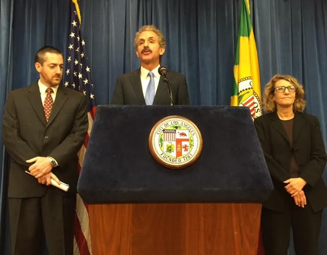 Three people at a podium in front of a dark blue curtain and an American flag and a State of California flag. Two men are wearing dark suits and ties. a woman is wearing a dark jacket and glasses.