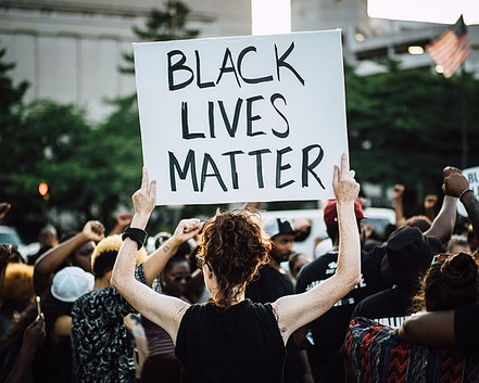 """Looking at a woman from behind, she is holding above her head a large sign that says, """"Black Lives Matter,"""" at a community rally."""