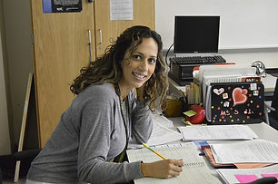 A teacher sitting at a desk grading papers.