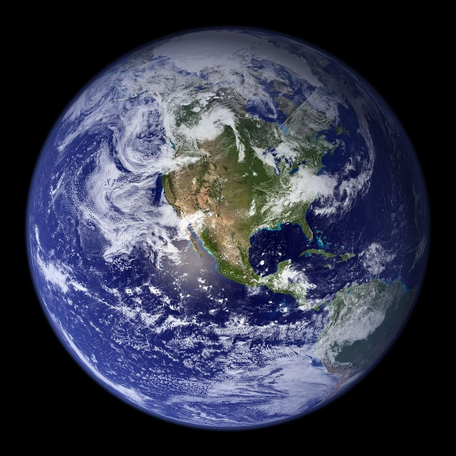 Stock photo of earth with lots of blue, white and green taken from space with a black and starry background.