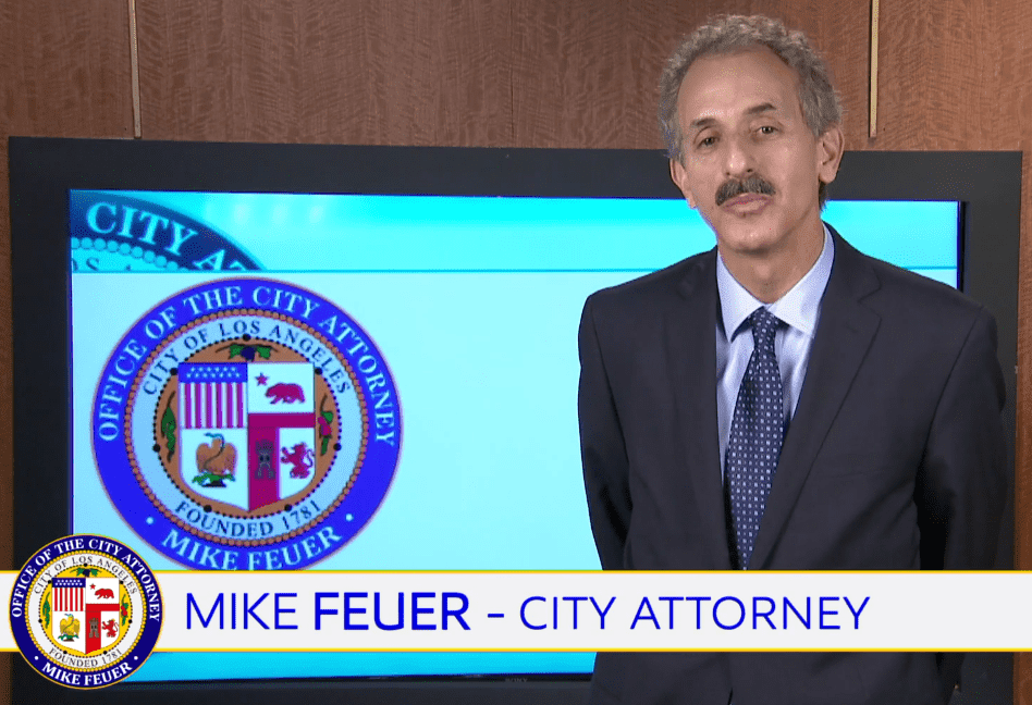photo of Mike Feuer, City Attorney, in front of video monitor