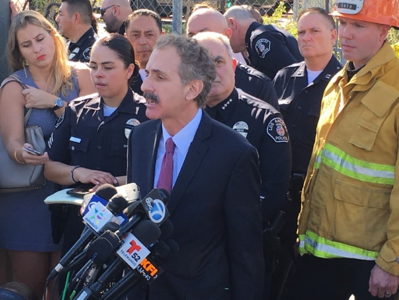 City Attorney Mike Feuer at the press conference following the February shooting at Sal Castro Middle School speaking into a large number of microphones and surrounded by reporters and law enforcement.