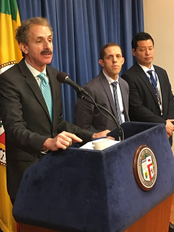 Los Angeles City Attorney Mike Feuer in a dark suit with a teal-colored tie speaking into a microphone and two other men in suits and ties to his right.