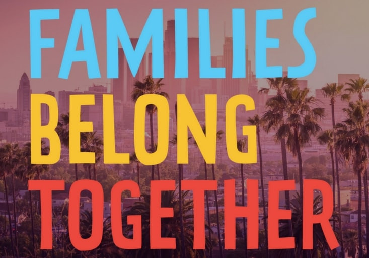 "Downtown Los Angeles with very large words in blue, yellow and red, ""families belong together"" over it."