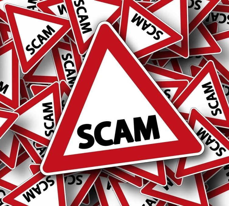 "Graphic of the word ""SCAM"" pictured as a road sign warning, atop a pile of smaller road signs with the word ""Scam"" on them.."