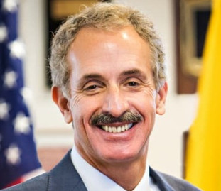Smiling man in a suit and tie and with a mustache; an official photo of City Attorney Mike Feuer, clicking it links to his bio.