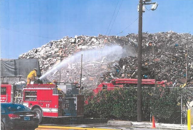 Enormous mountain of construction and demolition debris with a firefighter on a fire truck hosing it down.
