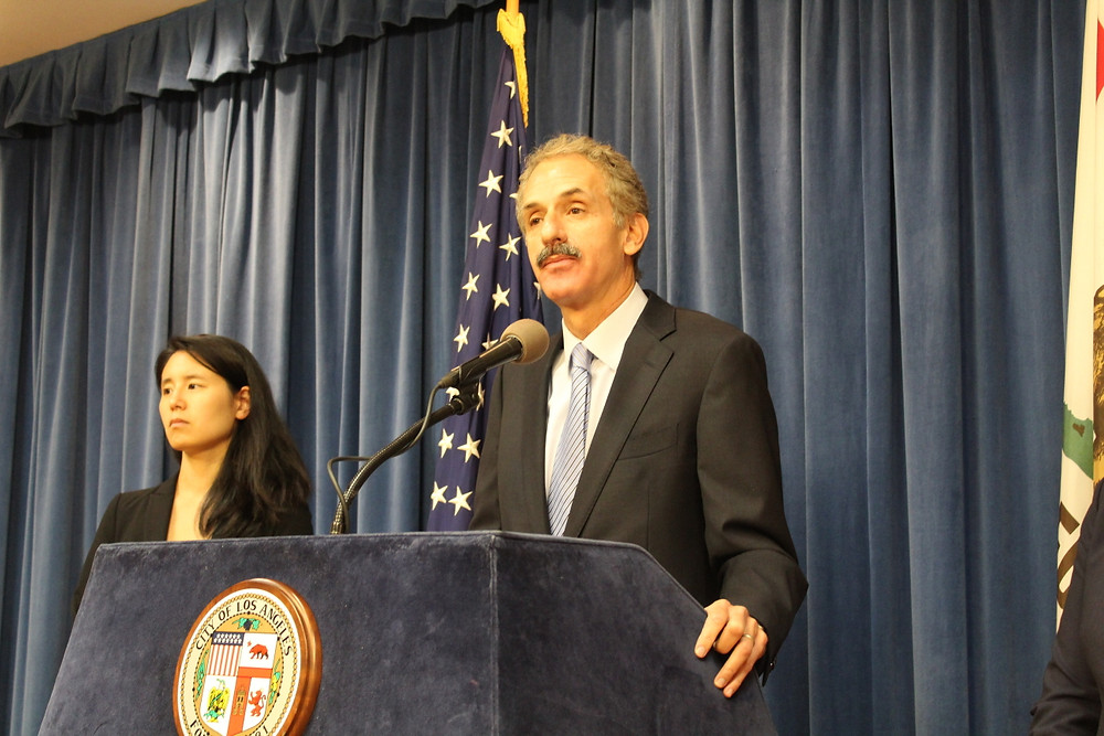City Attorney Mike Feuer at podium with Connie Chan of Affirmative Litigation.