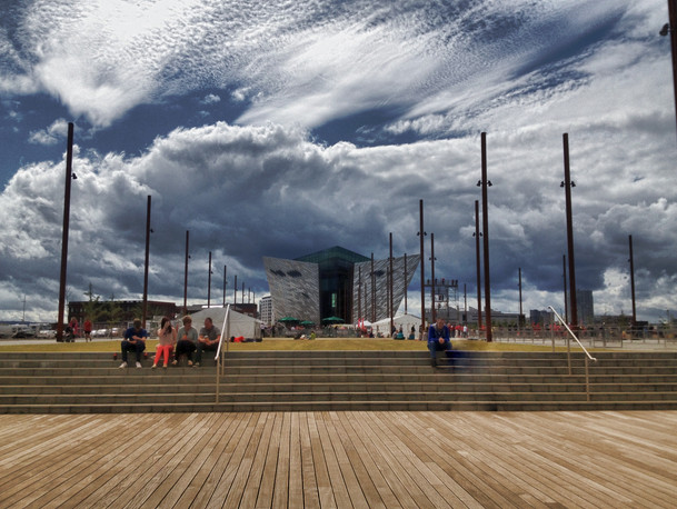 A view of Titanic Belfast while locals enjoy the sunny afternoon on the site where Titanic's stern would once rest while under construction.