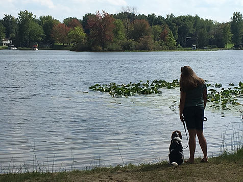 Dog trainer and her dog next to lake