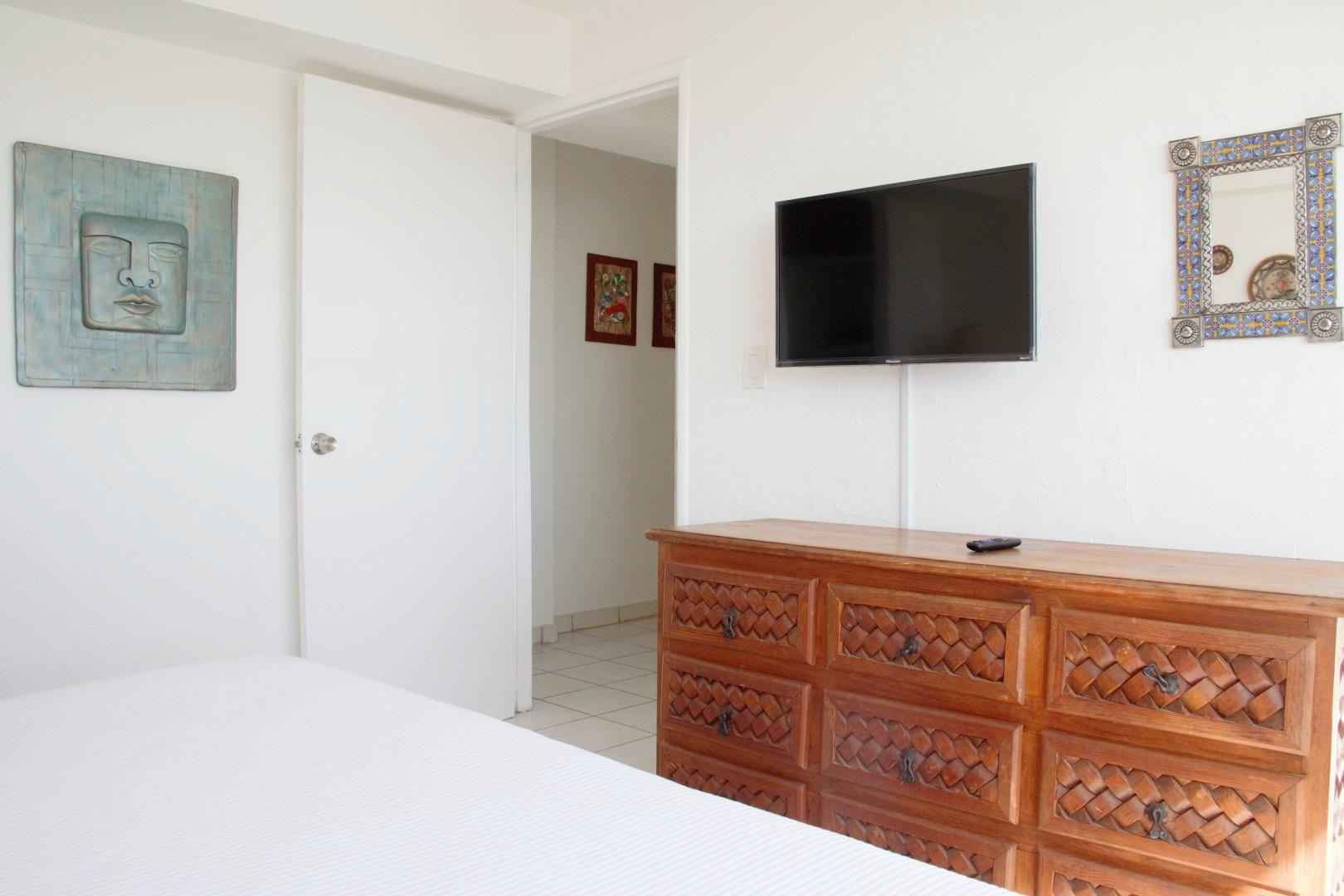 Dresser and smart TV in master bedroom.